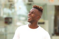 Закройте вверх по молодому чернокожему человеку смотря отсутствующий и смеяться над Стоковое Изображение RF