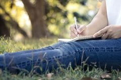 закройте вверх по молодым женщинам писать на тетради в парке, концепции в edu Стоковое фото RF