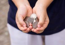 Закройте вверх по монетке в руке детей Стоковое Изображение RF