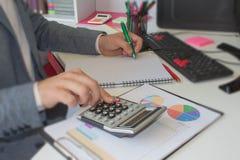 Закройте вверх по молодому человеку при калькулятор подсчитывая делающ примечания дома, рука пишет в тетради Стоковые Фотографии RF