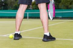 Закройте вверх по мужским ногам ` s игрока во время игры на суде зеленой травы Стоковые Изображения