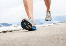 Закройте вверх по ногам бегуна изображения в идущих ботинках Стоковые Фото