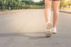 Закройте вверх по ногам женщины бежать на конкретной тропе на общественном парке с солнечным светом на заднем плане стоковая фотография rf