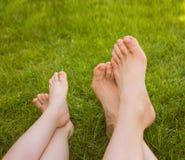 Закройте вверх по ногам женщины и ребенка лежа на траве Стоковые Фотографии RF