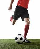 Закройте вверх по ногам футболиста в красных носках и черных ботинках бежать и пиная шарик стоковая фотография rf