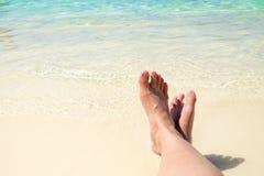 Закройте вверх по ноге креста путешественника босоногой кладя на shor пляжа на море Стоковое фото RF