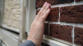 Закройте вверх по образцу руки человека касающему материала стены на торговом центре сток-видео