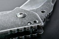 Закройте вверх половинного открытого черного складывая ножа на темной земле Стоковое Фото