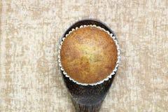 Закройте вверх по одиночному взгляд сверху хлебопекарни торта чашки банана на деревянном взгляде ковша очень вкусном на предпосыл Стоковое Изображение RF