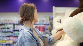 Закройте вверх по отснятому видеоматериалу девушки ища мягкие игрушки на полке в супермаркете Она определена с выбором сток-видео