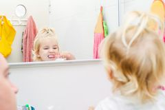 Закройте вверх по отцу и маленькой дочери малыша чистя ее зубы щеткой и смотря в зеркале в ванной комнате Отражение в зеркале Стоковое Изображение