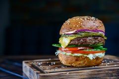 Закройте вверх по очень вкусному свежему бургеру на деревянной доске Стоковое Фото