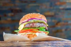 Закройте вверх по очень вкусному свежему бургеру на деревянной доске Стоковое фото RF