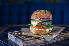 Закройте вверх по очень вкусному свежему бургеру на деревянной доске Стоковые Фотографии RF