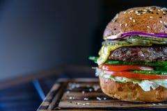 Закройте вверх по очень вкусному свежему бургеру на деревянной доске Стоковые Изображения RF
