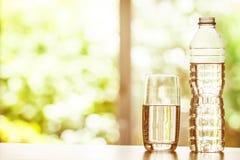 Закройте вверх по очищенной свежей воде питья от бутылки на таблице Стоковые Фотографии RF