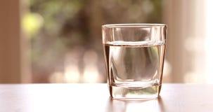 Закройте вверх по очищенной свежей воде питья от бутылки на таблице Стоковые Изображения