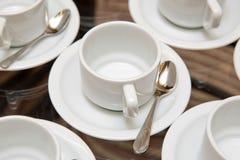 Закройте вверх по пакостной установке кофейной чашки и ложки на белых поддоннике и деревянном столе после выпивать в утре в винта Стоковое Изображение
