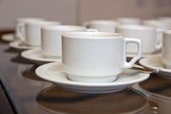 Закройте вверх по пакостной установке кофейной чашки и ложки на белых поддоннике и деревянном столе после выпивать в утре в винта Стоковое Фото