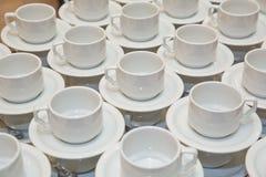 Закройте вверх по пакостной установке кофейной чашки и ложки на белых поддоннике и деревянном столе после выпивать в утре в винта Стоковые Фото