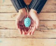 Закройте вверх по пасхальным яйцам удерживания и персоны женщины руки на деревянной таблице Стоковые Фотографии RF