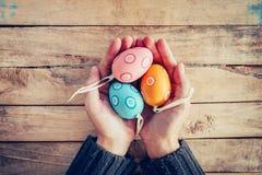 Закройте вверх по пасхальным яйцам удерживания и персоны женщины руки на деревянной таблице Стоковые Фото