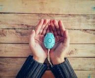 Закройте вверх по пасхальным яйцам удерживания и персоны женщины руки на деревянной таблице Стоковое фото RF