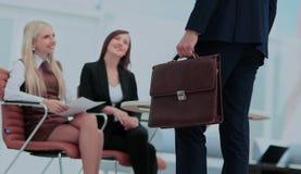 Закройте вверх по портрету бизнесмена с портфелем и коллегой Стоковое Изображение