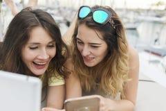 Закройте вверх по портрету 2 возбужденных подруг при мобильные телефоны лежа вниз и смеясь над и смотря в камере Стоковые Изображения RF