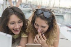 Закройте вверх по портрету 2 возбужденных подруг при мобильные телефоны лежа вниз и смеясь над и смотря в камере Стоковое фото RF