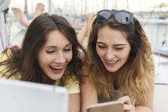 Закройте вверх по портрету 2 возбужденных подруг при мобильные телефоны лежа вниз и смеясь над и смотря в камере Стоковое Изображение RF