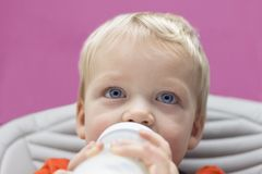 Закройте вверх по портрету голубоглазого малыша выпивая его бутылку стоковое фото rf