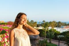 Закройте вверх по портрету девочка-подростка в парке во время солнечного дня, смотря и усмехаясь против неба и моря Стоковая Фотография RF