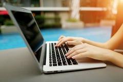 Закройте вверх по портрету кнопок клавиатуры отжимать рук женщины на бассейне солнечного дня компьтер-книжки Стоковые Изображения RF