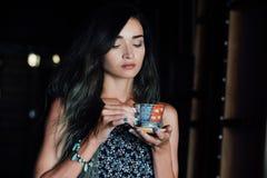 Закройте вверх по портрету кофе девушки выпивая в винтажном кафе на террасе в Азии Стоковые Изображения
