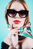 Закройте вверх по портрету красивой девушки в солнечных очках в студии на голубой предпосылке Стоковая Фотография RF