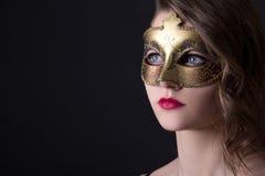 Закройте вверх по портрету красивой женщины в маске над серым цветом Стоковая Фотография
