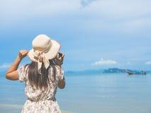 Закройте вверх по портрету красивой женщины при ретро камера битника имея потеху на пляже Стоковое фото RF