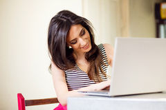 Закройте вверх по портрету красивой молодой женщины смотря компьтер-книжку Стоковая Фотография RF