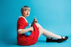 Закройте вверх по портрету красивой dollish девушки при короткие светло-фиолетовые волосы нося красное платье держа гавайскую гит Стоковое Фото