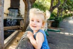 Закройте вверх по портрету маленькой blondy девушки малыша усмехаясь на камере Счастливый ребенк идя outdoors в парк или зоопарк  Стоковое Фото
