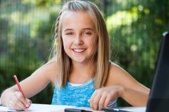 Портрет милой девушки делая домашнюю работу outdoors. Стоковое Фото