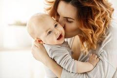 Закройте вверх по портрету молодой привлекательной матери целуя его плача младенца Ребенк смотря в сторону с устрашенным выражени Стоковые Изображения RF