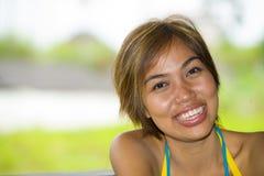 Закройте вверх по портрету молодой счастливый и красивый выразительный азиатский усмехаться женщины возбужденный и славный в поло Стоковые Фотографии RF