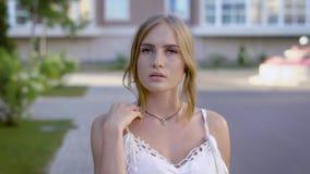 Закройте вверх по портрету молодой красивой белокурой женщины в белом платье шнурка усмехаясь на прогулке, расчешите ее вьющиеся  сток-видео