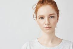 Закройте вверх по портрету молодой красивой девушки redhead в белой рубашке усмехаясь смотрящ камеру скопируйте космос Изолирован стоковое фото rf
