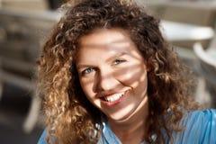 Закройте вверх по портрету молодой красивой усмехаясь девушки сидя на кафе в лучах солнца Стоковое фото RF
