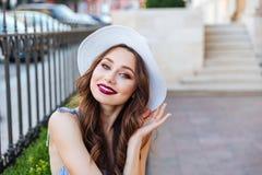 Закройте вверх по портрету молодой усмехаясь девушки сидя outdoors Стоковые Фото