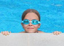 Закройте вверх по портрету предназначенной для подростков девушки в стеклах сини плавая полагаясь из бассейна Стоковая Фотография