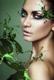 Закройте вверх по портрету сексуальной женщины в выплеске зеленого растения Стоковые Изображения RF
